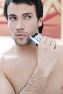 Young man using electric razor, portrait - VRF00062