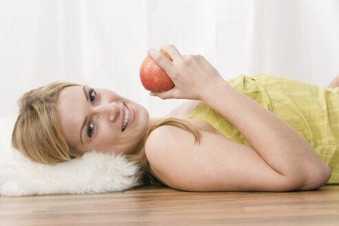 Blonde woman holding an apple, portrait - LDF00574