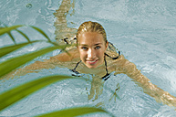 Young woman in swimming pool, smiling, portrait - HHF02353