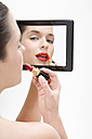 Young woman putting makeup on, portrait - MAEF00999