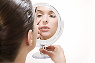 Young woman looking into mirror, portrait - MAEF00991