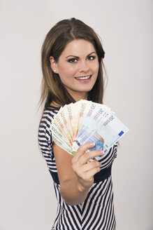 Young woman holding money, smiling, portrait - RDF00346