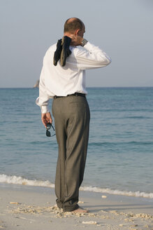 Asia, Thailand, Businessman standing at beach, rear view - RDF00685