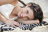 Asia, Thailand, Young woman lying on beach, smiling, portrait - RDF00665