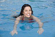 Asia, Thailand, Young woman in swimming pool, smiling, portrait - RDF00627