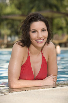 Asia, Thailand, Young woman in pool, smiling, portrait - RDF00624