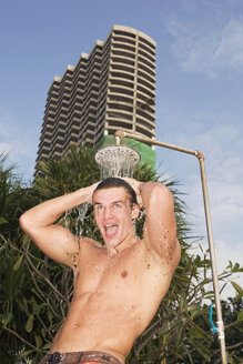 Asia, Thailand, Young man showering outdoors, portrait - RDF00602