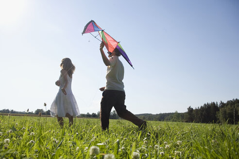 Germany, Bavaria, Young couple flying kites in meadow - RDF00592