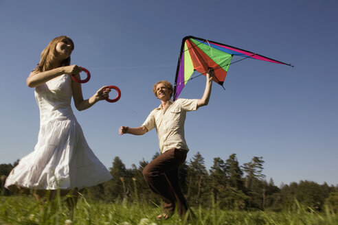 Germany, Bavaria, Young couple flying kites in meadow - RDF00589