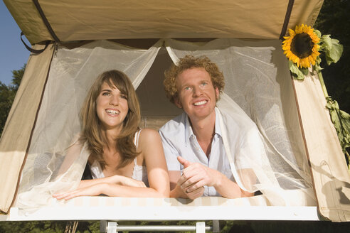 Germany, Bavaria, Young couple laying in tent - RDF00580