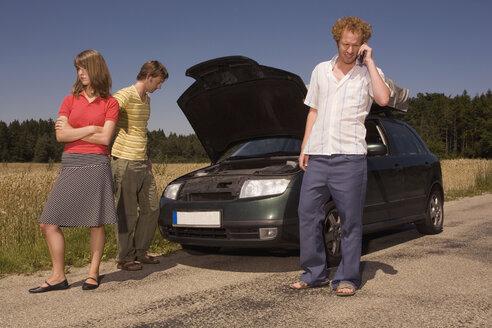 Germany, Bavaria, Three friends with broken down car - RDF00562