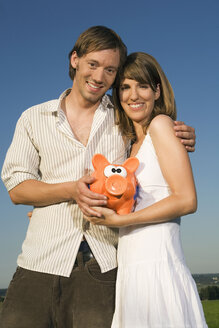 Germany, Bavaria, Young couple holding piggy bank, smiling, portrait - RDF00530