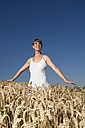 Germany, Bavaria, Young woman standing in field - RDF00520