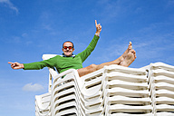 Belgium, Man sitting on stacked sunlounger, cheering, portrait - GWF00730