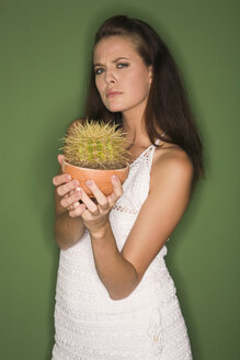 Young woman holding a cactus, frowning - RDF00772
