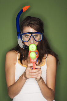 Young woman wearing diving goggles, holding a water pistol - RDF00760