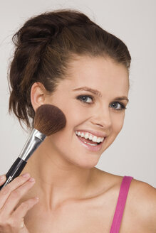 Young woman using a makeup brush - RDF00730
