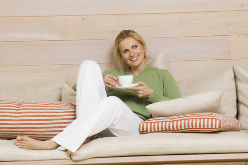 Young woman holding cup of coffee, smiling, portrait - WESTF07974