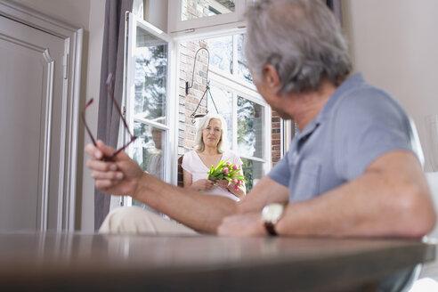 Senior man sitting at table, senior woman standing in the doorway, portrait - WESTF08226