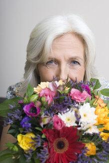 Senior woman holding bunch of flowers, portrait - WESTF08378