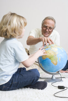 Grandfather and grandson (8-9) looking at globe - WESTF08327