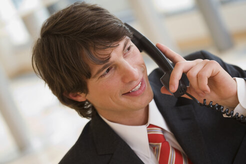 Young businessman using phone, portrait - HKF00265