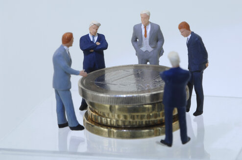 Business men figurines looking at coins - ASF03676