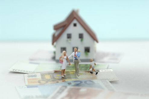 Pastic figurines on banknotes, house in background - ASF03661