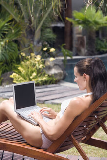 Young woman using laptop at swimming pool - ABF00365