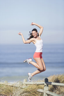 Young woman jumping on beach - ABF00323