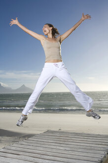 South Africa, Cape Town,Young woman jumping on beach - ABF00278