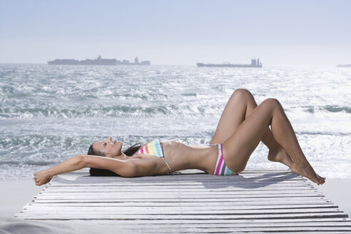 Young woman lying on jetty, portrait - ABF00259