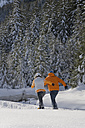 Austria, Salzburger Land, Altenmarkt-Zauchensee, Young couple snowshoeing, rear view - HH02528