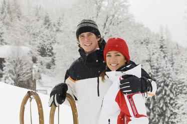 Austria, Salzburger Land, Altenmarkt-Zauchensee, Young couple with sledge, portrait - HH02542