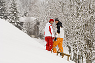 Austria, Salzburger Land, Altenmarkt-Zauchensee, Young couple pulling sledge - HH02539