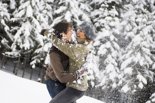 Austria, Salzburger Land, Altenmarkt, Young couple in snowscape, fooling about - HH02586