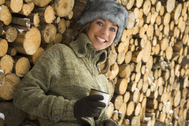 Austria, Salzburger Land, Altenmarkt, Young woman leaning against stacked firewood - HH02571