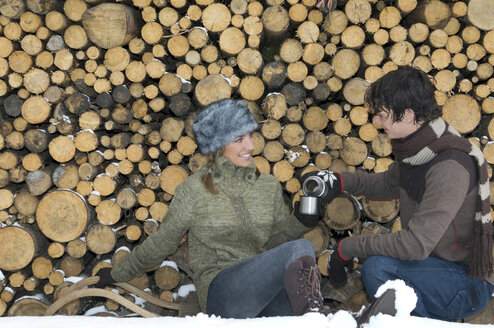 Austria, Salzburger Land, young couple taking a break at  stack of wood - HH02567