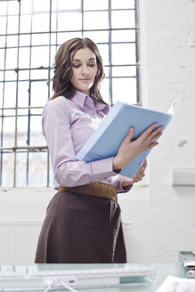 Young businesswoman working in office, holding documents - BMF00376