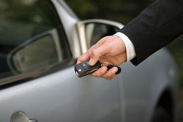 Person at car using remote control key, close-up - GAF00082