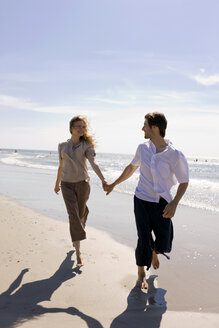 Germany, Baltic sea, Young couple walking across beach, holding hands - WESTF09261
