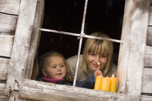 Austria, Salzburger Land, Mother and daughter (3-4) lighting candles on windowsill - HHF02679