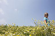 Woman walking across camomile field - GWF00811