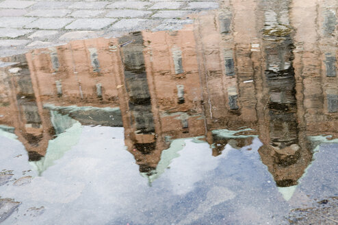 Germany, Hamburg, Old warehouse district, buildings reflected in puddle on road - AWDF00010