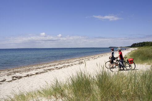 Denmark, Fuenen, Mountainbikers taking a break on the coast - DSF00185