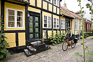 Denmark, Fuenen, Couple mountain biking alongside timbered houses - DSF00182