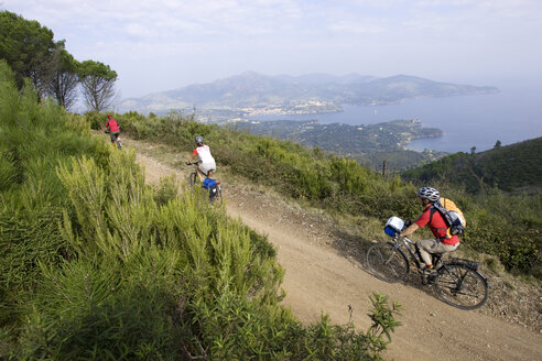 Italy, Tuscany, Elba, Mountainbikers riding across coastal path - DSF00158