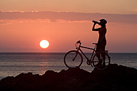 Italy, Tuscany, Albegna, Female mountainbiker taking a break at sunset - DSF00149