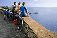 Italy, Tuscany, Monte Argentario, Mountainbikers looking on to the sea - DSF00146