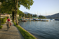 Germany, Bavaria, Tegernsee, Woman mountainbiking lakeside - DSF00137